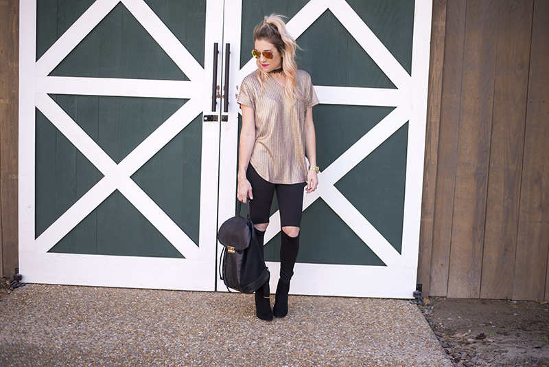New Years Eve Looks: Casual featuring a sparkly gold top, black cutout leggings and black booties. Minimum jewelry with a black lace choker and gold watch.