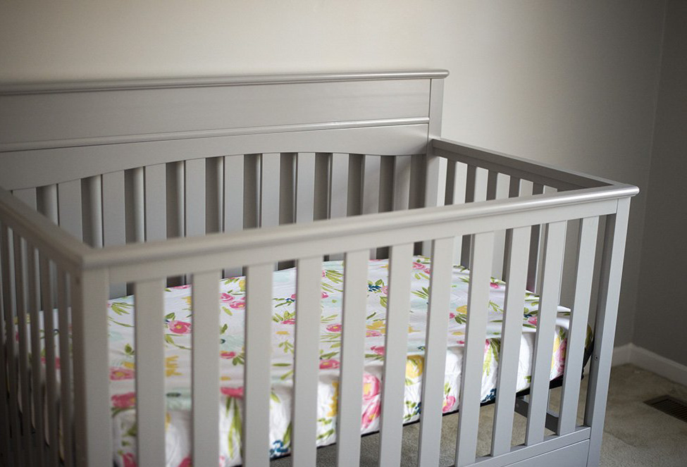 Gray crib for a baby girl nursery.
